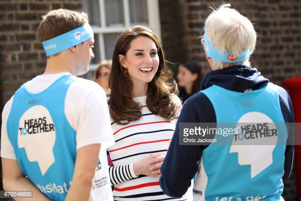 Catherine Duchess of Cambridge speaks with runners after they put a Heads Together headband onto the Kensington Palace postbox in support of the...
