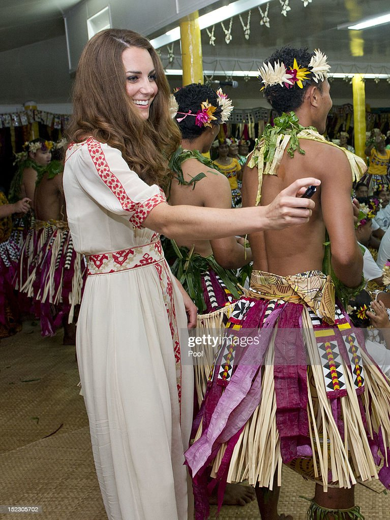 Catherine, Duchess of Cambridge sprays perfume on the dancers at the Vaiku Falekaupule for an entertainment programme on September 18, 2012 in Tuvalu. Prince William, Duke of Cambridge and Catherine, Duchess of Cambridge are on a Diamond Jubilee tour representing the Queen taking in Singapore, Malaysia, the Solomon Islands and Tuvalu.