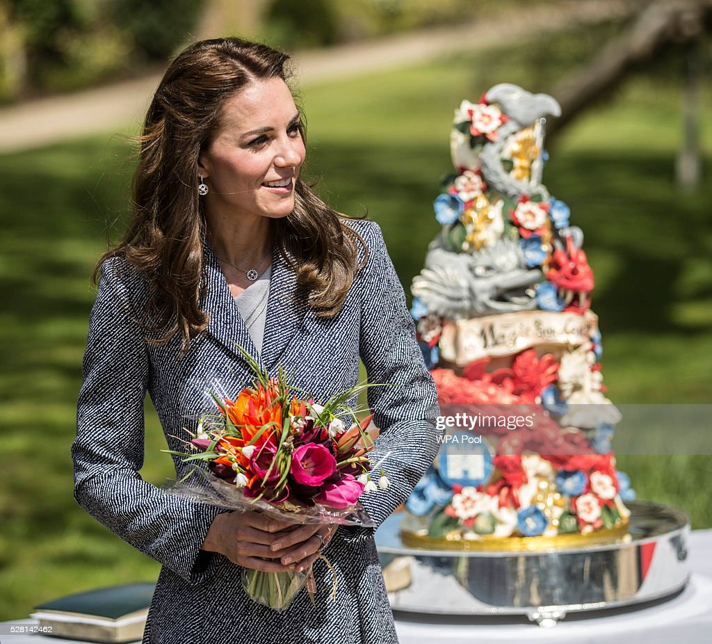 Catherine, Duchess of Cambridge stands next to an ornate cake decorated with dragons and magical creatures baked especially for the opening as she officially opens The Magic Garden at Hampton Court Palace on May 4, 2016 in London, England.