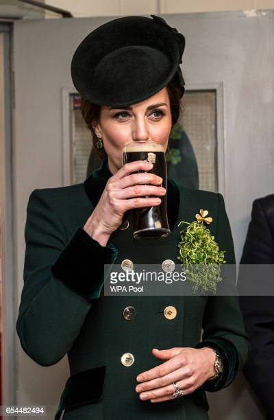 Catherine Duchess of Cambridge takes a drink of Guinness as she meets with soldiers of the 1st battalion Irish Guards in their canteen following...