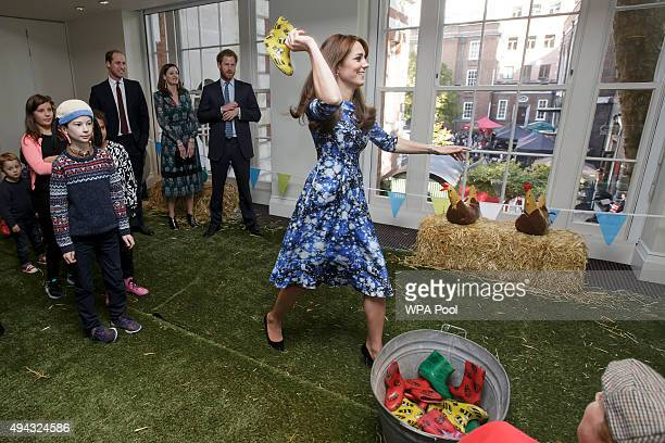 Catherine Duchess of Cambridge takes part in welly wanging watched by the Prince William Duke of Cambridge back left and Prince Harry centre with...