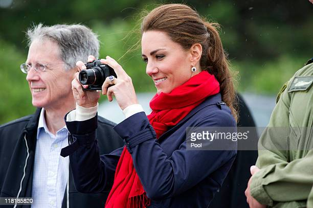 Catherine Duchess of Cambridge takes photographs as Prince William Duke of Cambridge takes part in helicopter manouvres called 'water birding' across...