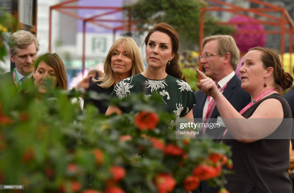 Catherine, Duchess of Cambridge (C), talks to an exhibitor (R) as she visits the RHS Chelsea Flower Show press day at Royal Hospital Chelsea on May 22, 2017 in London, England. The prestigious Chelsea Flower Show, held annually since 1913 in the Royal Hospital Chelsea grounds, is open to the public from the 23rd to the 27th of May, 2017.