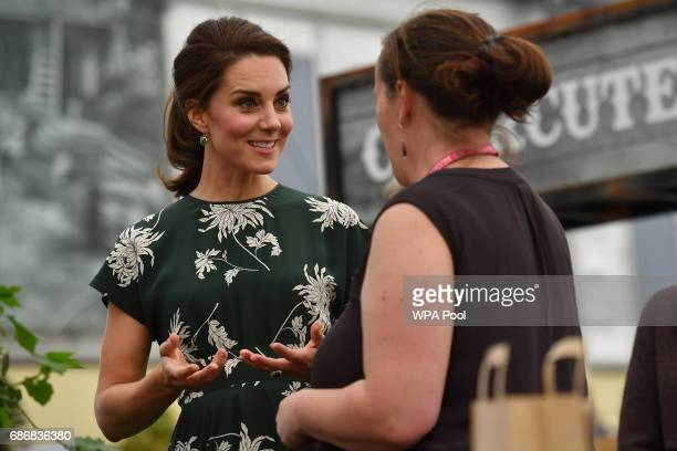 Catherine Duchess of Cambridge talks to an exhibitor as she visits the RHS Chelsea Flower Show press day at Royal Hospital Chelsea on May 22 2017 in...