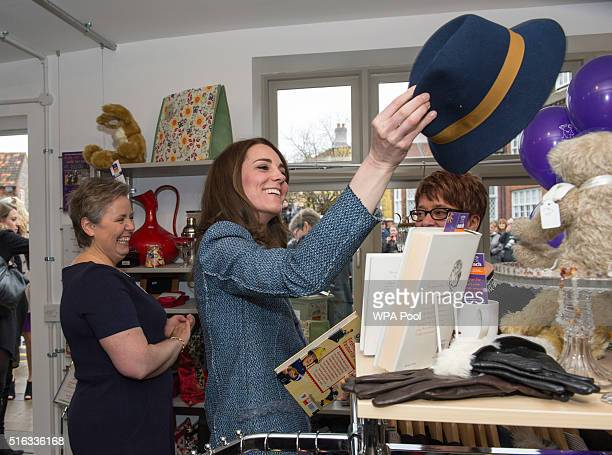 Catherine Duchess of Cambridge tries on a Boden hat priced at £15 as she takes a tour of the new EACH charity shop that she officially opened earlier...