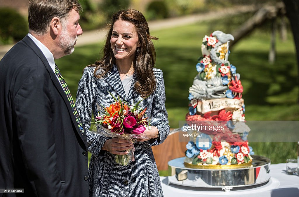 Catherine, Duchess of Cambridge walks past an ornate cake decorated with dragons and magical creatures baked especially for the opening as she officially opens The Magic Garden at Hampton Court Palace on May 4, 2016 in London, England.