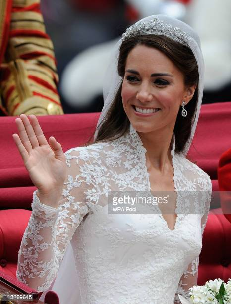 Catherine Duchess of Cambridge waves as she travels beside husband Prince William Duke of Cambridge in the 1902 State Landau carriage on the...