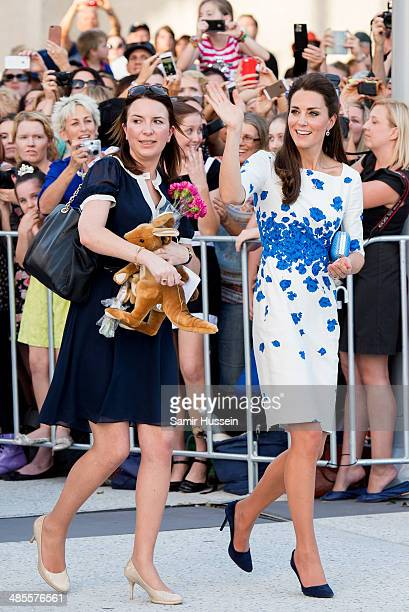Catherine Duchess of Cambridge waves at the crowds as personal assistant Rebecca Deacon carries gifts during a walkabout on April 19 2014 in Brisbane...