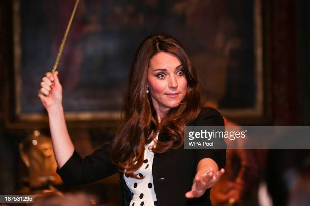 Catherine Duchess of Cambridge waves her wand on the set used to depict Diagon Alley in the Harry Potter Films during the Inauguration Of Warner Bros...