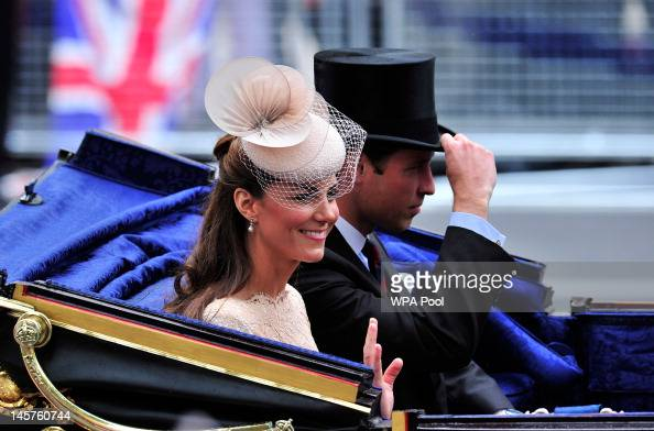 Catherine Duchess of Cambridge waves next to Prince William Duke of Cambridge in the 1902 State Landau coach during the carriage procession from...
