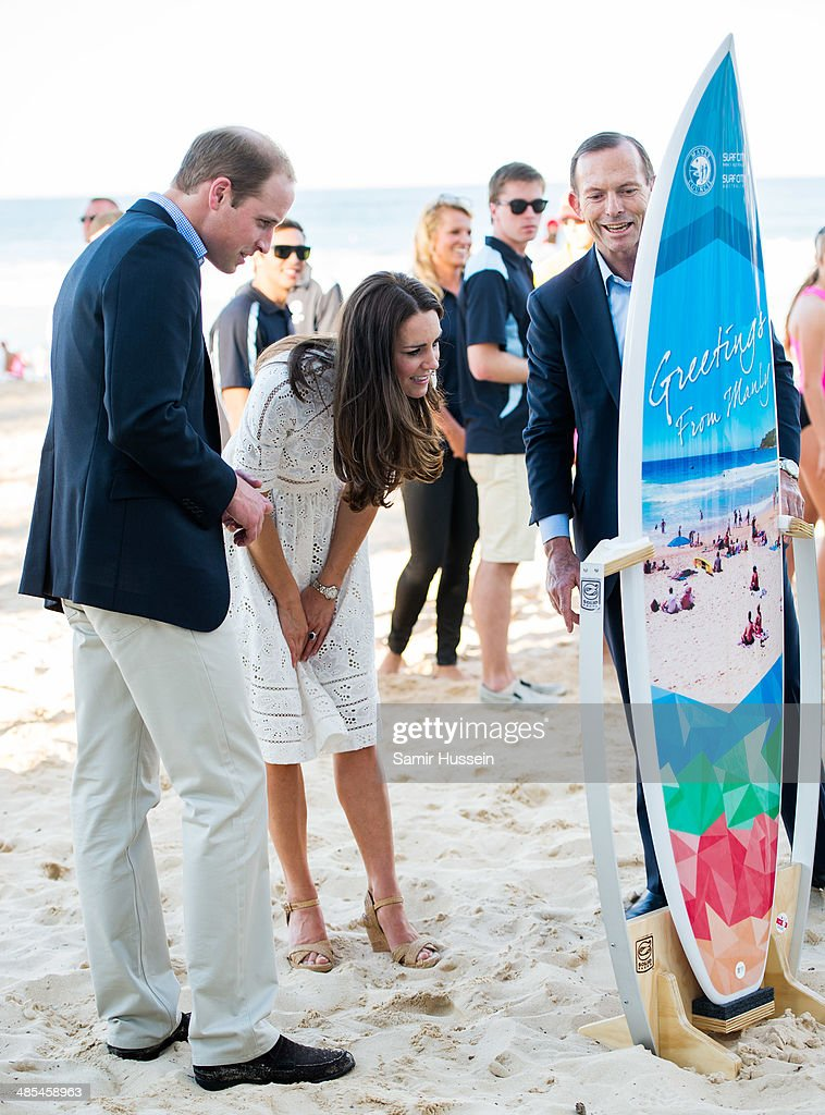 Catherine, Duchess of Cambridgeand Prince William, Duke of Cambridge look at a surfboard they were given with Australian Prime Minister Tony Abbott (R) as they attend a lifesaving event on Manley Beach on April 18, 2014 in Sydney, Australia. The Duke and Duchess of Cambridge are on a three-week tour of Australia and New Zealand, the first official trip overseas with their son, Prince George of Cambridge.