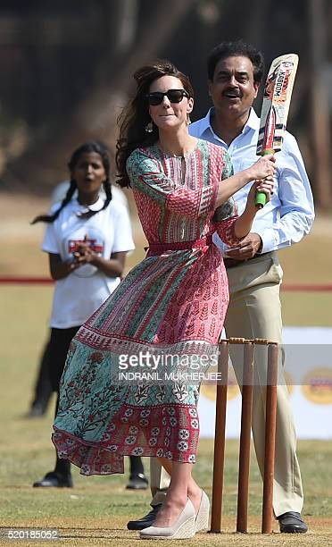 Catherine Duchess of Cambridgelooks on as she and an unseen Prince William Duke of Cambridge play a game of cricket with Indian children who are...