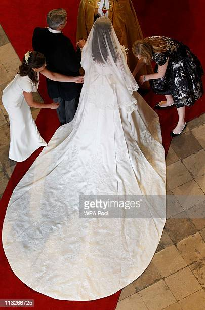 Catherine Middleton has her dress adjusted by her sister and Maid of Honor Pippa Middleton as she arrives with her father Michael Middleton before...