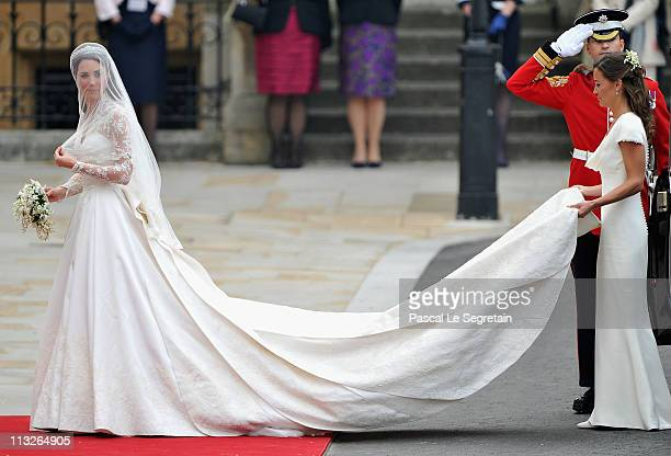 Catherine Middleton looks to the crowds as her sister and Maid of Honour Pippa Middleton holds her dress before walking in to the Abbey to attend the...