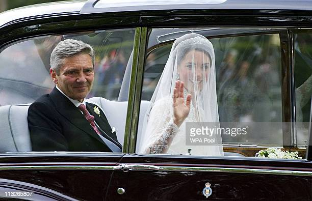 Catherine Middleton waves as she travels in a Rolls Royce Phantom VI accompanied by her father Michael Middleton to Westminster Abbey ahead of the...