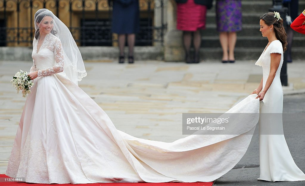 Catherine Middleton waves to the crowds as her sister and Maid of Honour <a gi-track='captionPersonalityLinkClicked' href=/galleries/search?phrase=Pippa+Middleton&family=editorial&specificpeople=4289296 ng-click='$event.stopPropagation()'>Pippa Middleton</a> holds her dress before walking in to the Abbey to attend the Royal Wedding of Prince William to Catherine Middleton at Westminster Abbey on April 29, 2011 in London, England. The marriage of the second in line to the British throne is to be led by the Archbishop of Canterbury and will be attended by 1900 guests, including foreign Royal family members and heads of state. Thousands of well-wishers from around the world have also flocked to London to witness the spectacle and pageantry of the Royal Wedding.