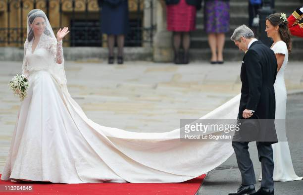 Catherine Middleton waves to the crowds as her sister and Maid of Honour Pippa Middleton holds her dress next to her father Michael Middleton before...