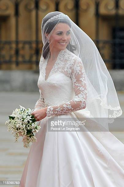 Catherine Middleton waves to the crowds as her sister and Maid of Honour Pippa Middleton holds her dress before walking in to the Abbey to attend the...