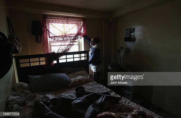 Catherine Orange opens the bedroom shades in her family's 13th floor apartment in the Red Hook housing project on November 3 2012 in the Brooklyn...