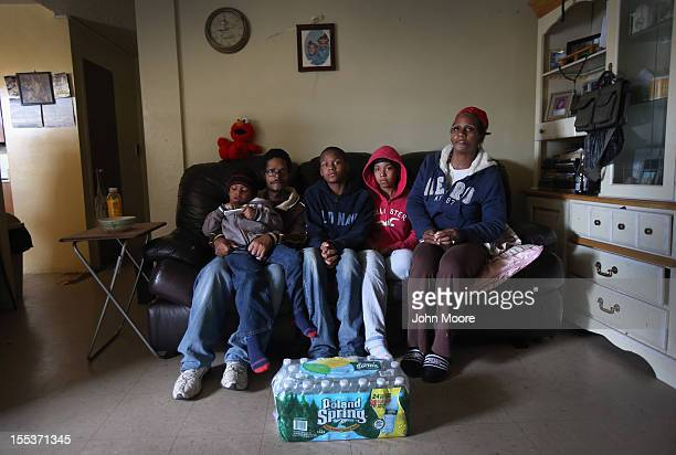 Catherine Orange sits with her family including her son Angel husband Jose son Jose and daughter Jada 17 in their 13th floor apartment in the Red...