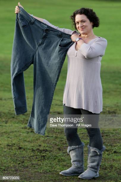 Catherine Powell from Alsager Cheshire holds a pair of her old jeans as she celebrates dropping eight dress sizes and shed more than eight stone in...