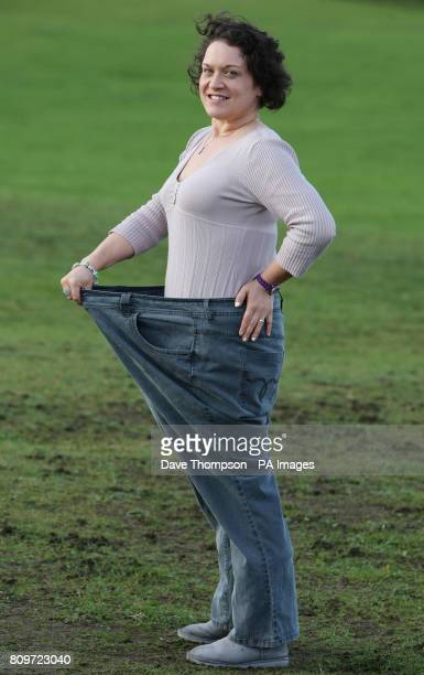 Catherine Powell from Alsager Cheshire wears a pair of her old jeans as she celebrates dropping eight dress sizes and shed more than eight stone in...