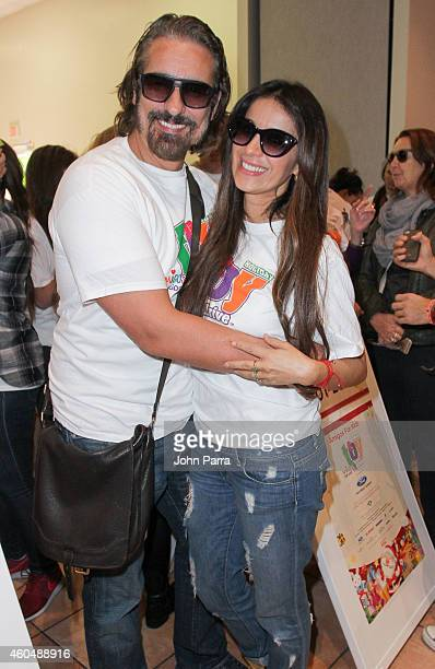 Catherine Siachoque and Miguel Varoni volunteer at the Amigos For Kids 23rd Annual Holiday Toy Drive on December 14 2014 in Miami Florida