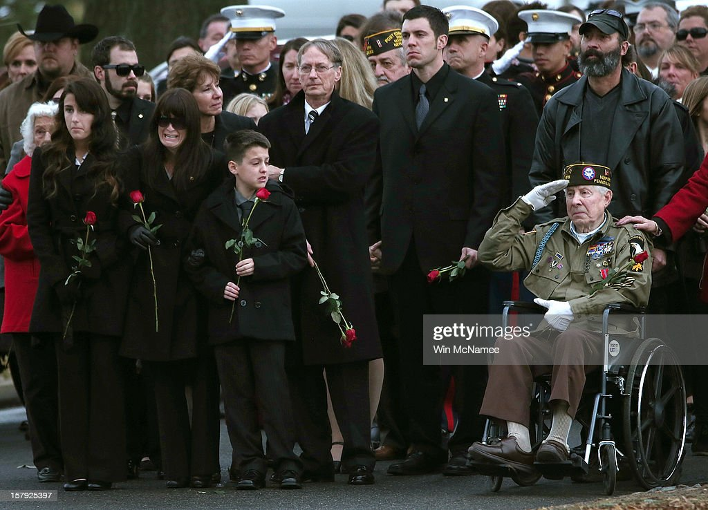 Catherine Stouffer (C), widow of Marine Chief Warrant Officer 3 Gary Stouffer, walks with her daughter Shannon (L) and her son Shane (R) during Stouffer's burial service at Arlington National Cemetery December 7, 2012 in Arlington, Virginia. Stouffer, a combat veteran formerly deployed in both Iraq and Afghanistan, was one of four veterans killed when the float they were riding on was hit by a train during a Veterans Day parade in Midland, Texas on November 15.