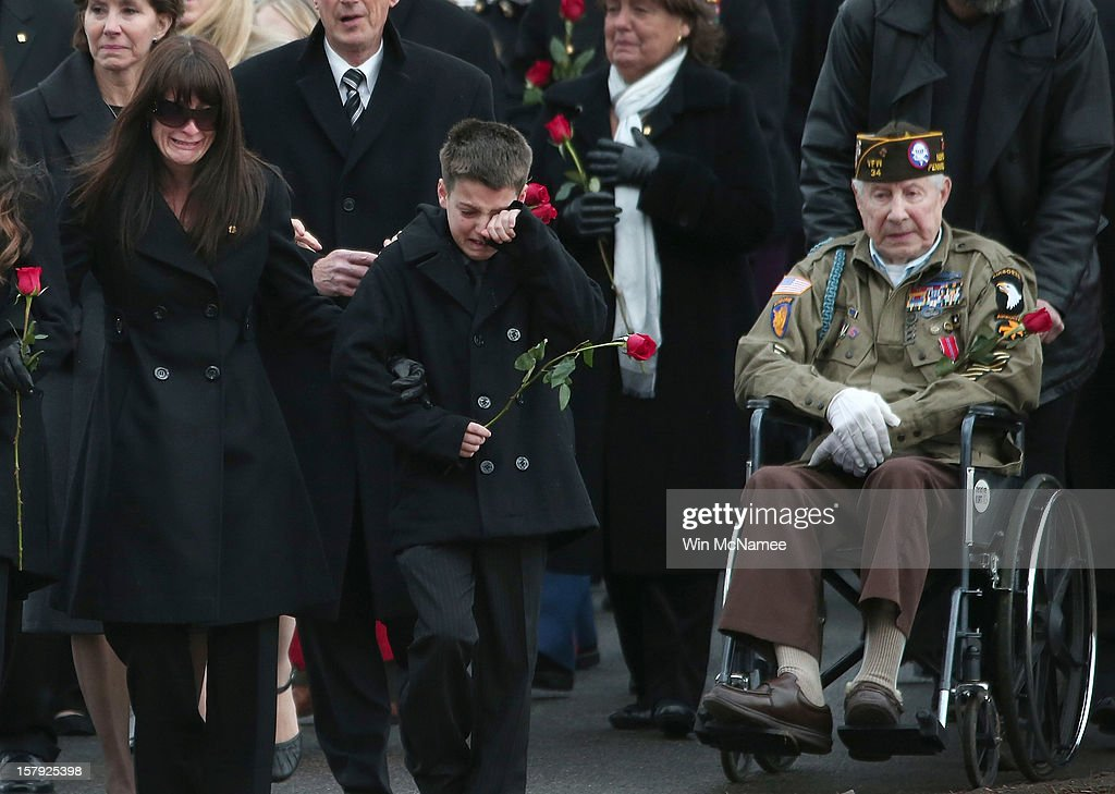 Catherine Stouffer (L), widow of Marine Chief Warrant Officer 3 Gary Stouffer, walks with her son Shane (C) during Stouffer's burial service at Arlington National Cemetery December 7, 2012 in Arlington, Virginia. Stouffer, a combat veteran formerly deployed in both Iraq and Afghanistan, was one of four veterans killed when the float they were riding on was hit by a train during a Veterans Day parade in Midland, Texas on November 15.
