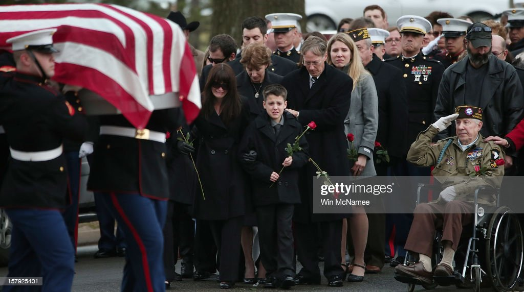 Catherine Stouffer (L), widow of Marine Chief Warrant Officer 3 Gary Stouffer, watches with her son Shane (C) as a Marine Corps honor guard carries Stouffer's casket during a burial service at Arlington National Cemetery December 7, 2012 in Arlington, Virginia. Stouffer, a combat veteran formerly deployed in both Iraq and Afghanistan, was one of four veterans killed when the float they were riding on was hit by a train during a Veterans Day parade in Midland, Texas on November 15.