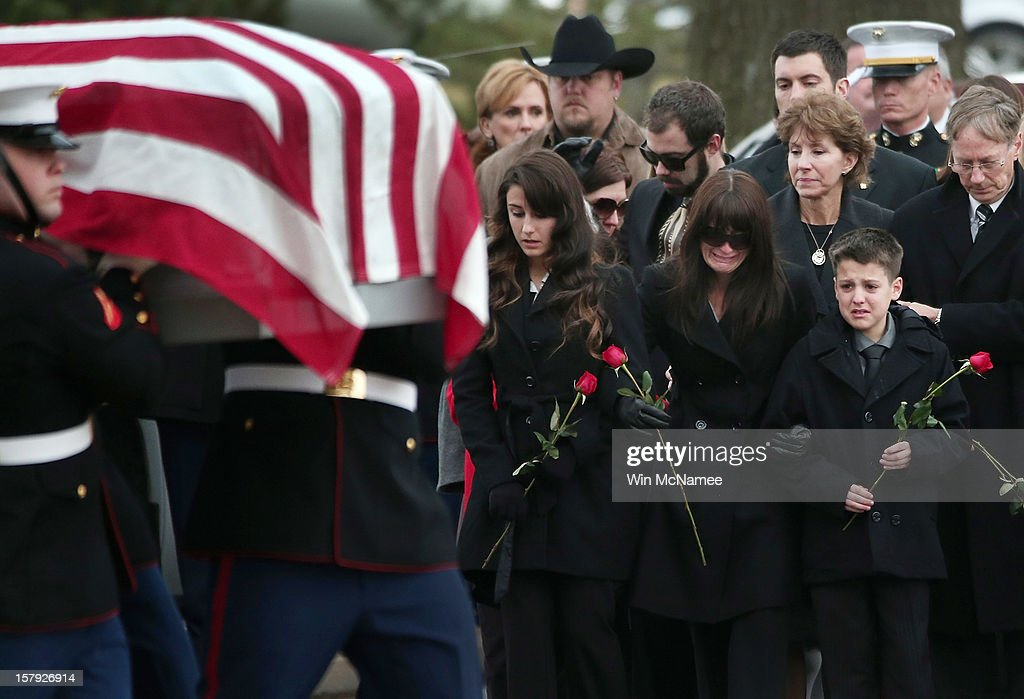 Catherine Stouffer (C), widow of Marine Chief Warrant Officer 3 Gary Stouffer, watches with daughter Shannon (L) and her son Shane (R) as a Marine Corps honor guard carries Stouffer's casket during a burial service at Arlington National Cemetery December 7, 2012 in Arlington, Virginia. Stouffer, a combat veteran formerly deployed in both Iraq and Afghanistan, was one of four veterans killed when the float they were riding on was hit by a train during a Veterans Day parade in Midland, Texas on November 15.