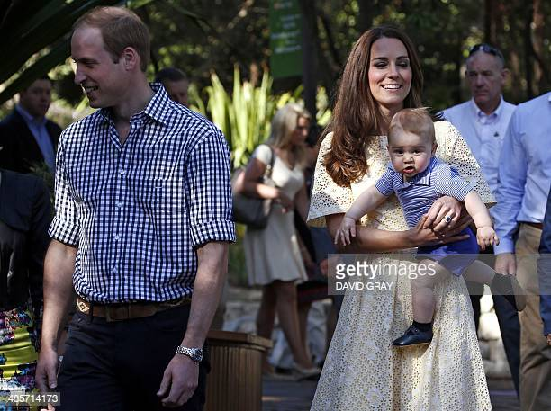 Catherine the Duchess of Cambridge holds her son Prince George as they visit with her husband Britain's Prince William the enclosure for the...