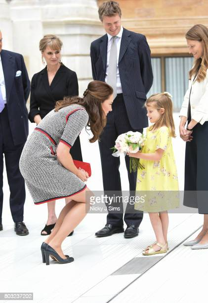 Catherine the Duchess of Cambridge is presented flowers by a young girl during an official visit to the new VA exhibition road quarter at Victoria...