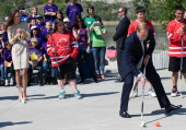 Catherine the Duchess of Cambridge looks on as Prince William Duke of Cambridge plays street hockey as they visit the Somba K'e Civic Plaza on day 6...