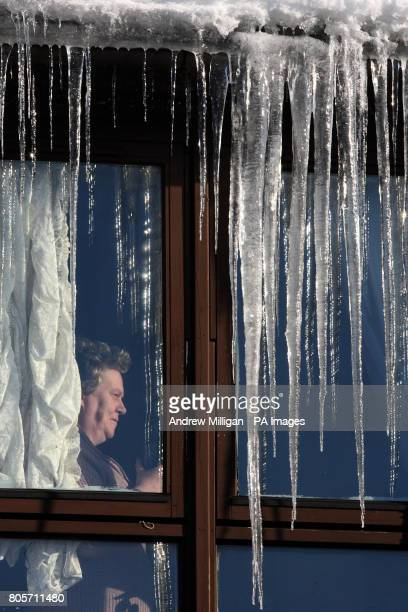 Catherine Turner looks out from a window in her house in Whitburn West Lothian as icicles form from the guttering after freezing temperatures...