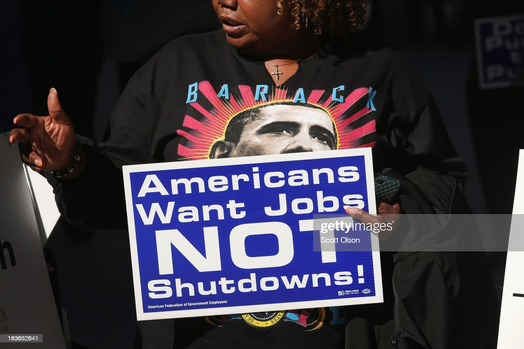 Catherine Wriddley carries a sign during a protest and prayer vigil held to call for an end to the federal government shutdown on October 8, 2013 in Chicago, Illinois. The protest was organized by the Rev. Jesse Jackson and the Rainbow PUSH Coalition as well as local labor, faith and community leaders.
