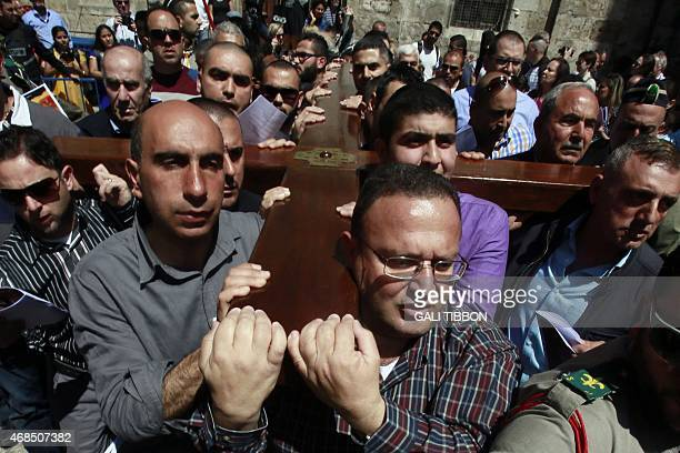 Catholic Arab worshippers of the local parish carry a wooden cross along the Via Dolorosa in Jerusalem's Old City during the Good Friday procession...