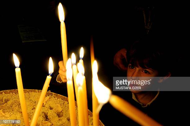 A Catholic boy lights candle at the St Esprit Church during the Christmas mass at midnight in Harbiye downtown Istanbul on December 25 2010 AFP...