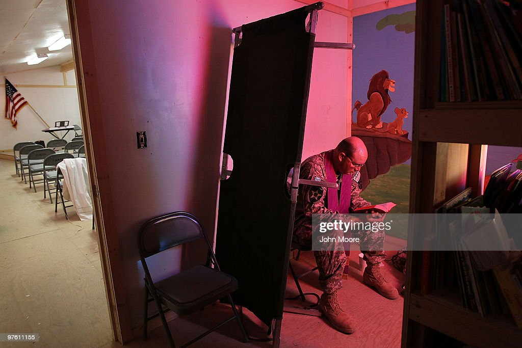 Catholic Chaplain Cpt. Carl Subler reads a prayer book behind an upturned bed cot while waiting to hear soldiers' anonymous confessions on March 10, 2010 at Forward Operating Base Ramrod in Kandahar province, Afghanistan. He was using a chapel room where soldiers read stories to their children while taped on video, which is then sent to their families at home. As the only Catholic chaplain in his brigade, Cpt. Subler travels between far-flung bases, celebrating mass and counseling Catholic soldiers accross southern Afghanistan.