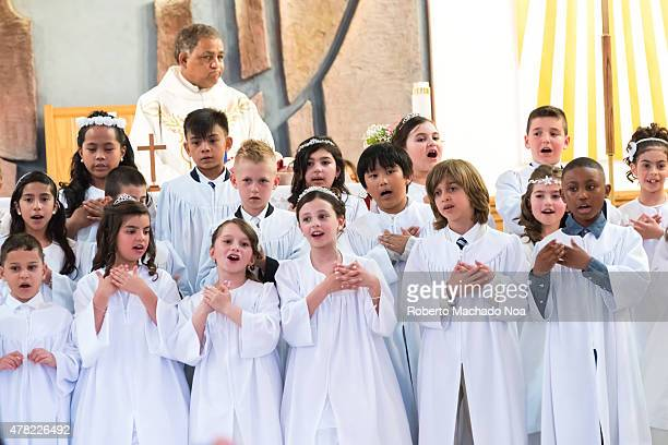 CENTRE TORONTO ONTARIO CANADA Catholic Children's choir dressed in white robes with a priest standing behind to instruct them