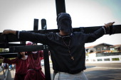 Catholic devotee carries a cross as a form of penance during holy week on April 17 2014 in Pampanga Philippines The brutal practice is a form of...