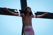 Catholic devotee grimaces in pain after being nailed to a cross during a reenacment of the crucifixion of Christ on Good Friday on April 18 2014 in...