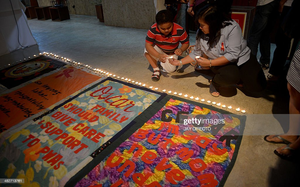 A Catholic devotee lights candles around quilts made by victims of HIV-AIDS who died of complication because of HIV-AIDS in a church in suburban Manila on December 1, 2013. The Department of Health in the Philippine recorded a total of almost 500 HIV-AIDS cases in October 2013, or 66 percent higher than the 295 cases in October 2012, making it the highest ever recorded in a month in the country. AFP PHOTO / Jay DIRECTO
