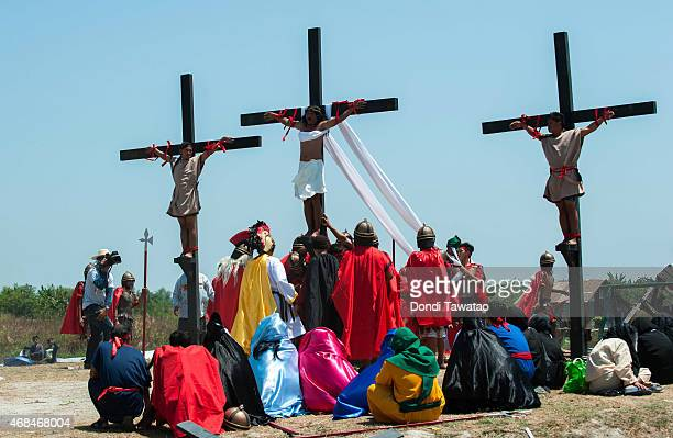 Catholic devotee nailed to a cross is hoisted by participants during a reenactment of the crucifixion of Christ on Good Friday on April 3 2015 in San...