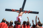 Catholic devotee nailed to a cross is hoisted by participants during a reenacment of the crucifixion of Christ on Good Friday on April 18 2014 in San...
