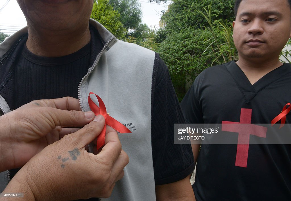 A Catholic devotee pins a symbol for aids awareness to mark World AIDS Day with a mass in a church in suburban Manila on December 1, 2013. The Department of Health in the Philippine recorded a total of almost 500 HIV-AIDS cases in October 2013, or 66 percent higher than the 295 cases in October 2012, making it the highest ever recorded in a month in the country. AFP PHOTO / Jay DIRECTO