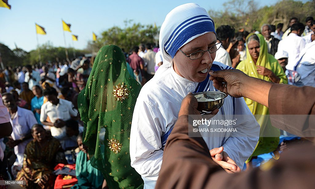 A Catholic devotee receives 'holy communion' during the annual pilgrimage at Saint Anthony's Church on Katchchativu Island in the northern waters of Jaffna on February 24, 2013. Roman Catholic pilgrims from neighbouring India also joined in the service to celebrate the shrine's annual church feast, which was suspended for much of the three-decade conflict. AFP PHOTO / Ishara S. KODIKARA
