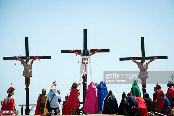 Catholic devotees are hoisted up onto a cross by participants during a reenactment of the crucifixion of Christ on Good Friday on April 3 2015 in San...