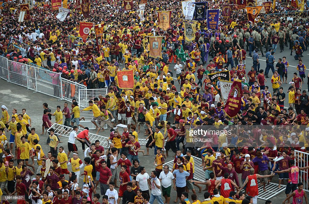 Catholic devotees break steel barriers as they try to reach the grandstand where the statue of the Black Nazarene (not pictured) was displayed prior to the annual procession in honor of the centuries-old icon of Jesus Christ, in Manila on January 9, 2013. Masses of Catholic devotees swept through the Philippine capital on January 9, in a spectacular outpouring of passion for a centuries-old icon of Jesus Christ that many believe can perform miracles. AFP PHOTO/TED ALJIBE
