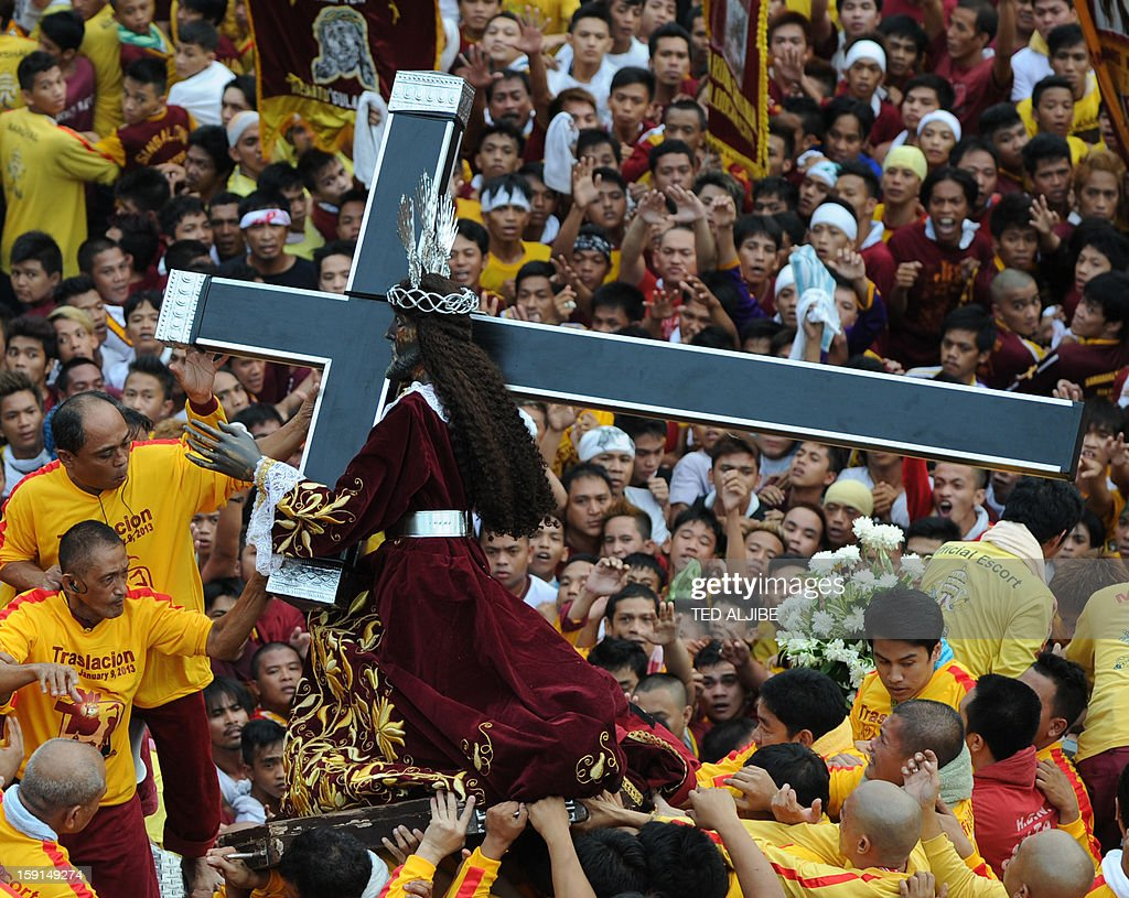 Catholic devotees carry the life-size statue of the Black Nazarene (C) to a carriage during an annual procession in honor of the centuries-old icon of Jesus Christ in Manila on January 9, 2013. Masses of Catholic devotees swept through the Philippine capital on January 9, in a spectacular outpouring of passion for a centuries-old icon of Jesus Christ that many believe can perform miracles. AFP PHOTO/TED ALJIBE